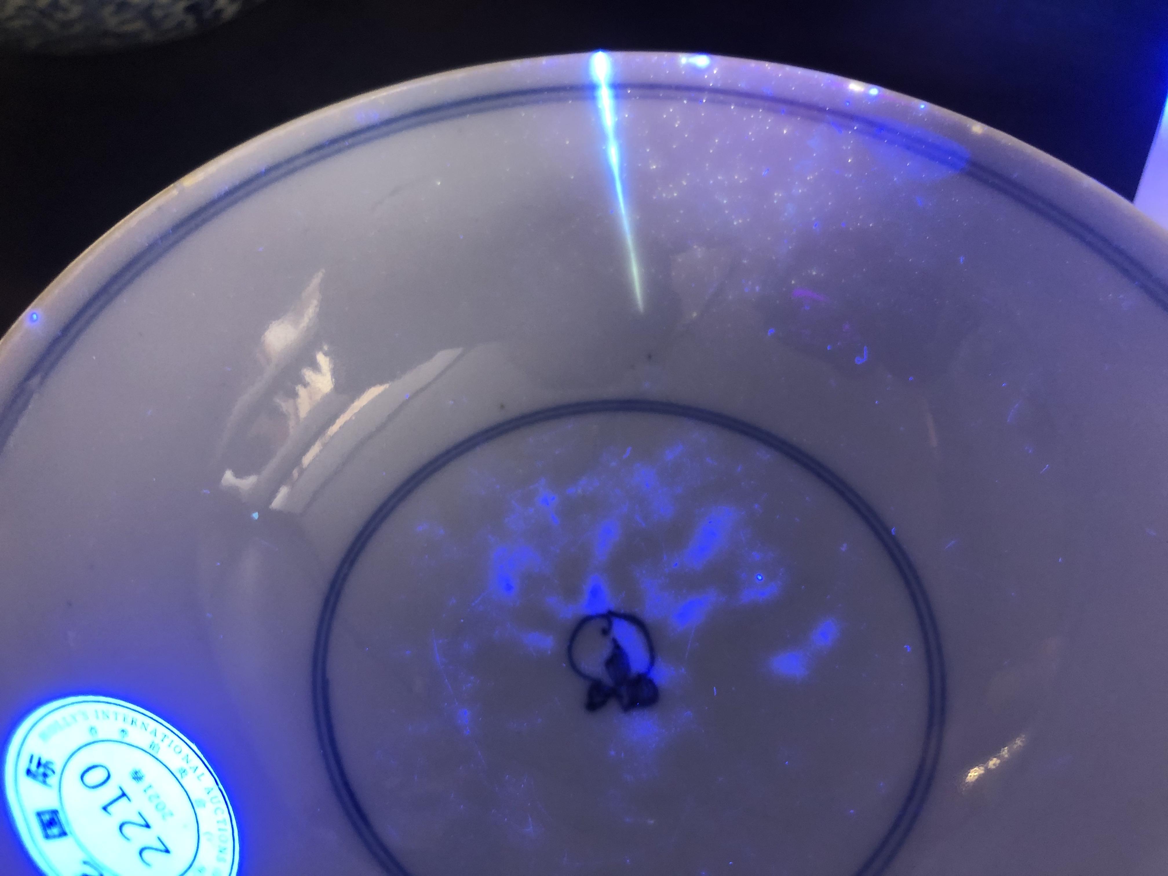 在藍光燈照射下,牛先生競買的瓷碗上有裂紋顯現。