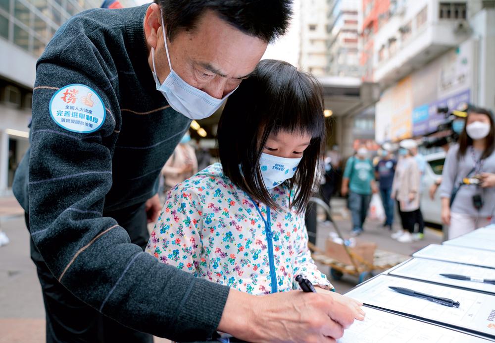 3月12日,香港湾仔,市民周先生带着 6岁的女儿来到签名桌前和女儿一起写下名字 王申摄 / 本刊