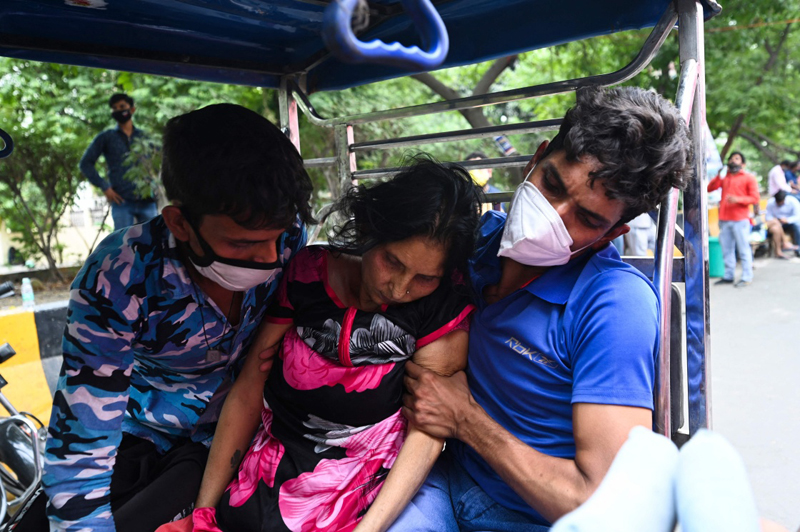 当地时间2021年5月4日,印度加济阿巴德,两名男子帮助一名新冠患者前去吸氧。印度卫生部4日公布的数据显示,截至当日9时,全国累计新冠确诊病例超过2000万例。
