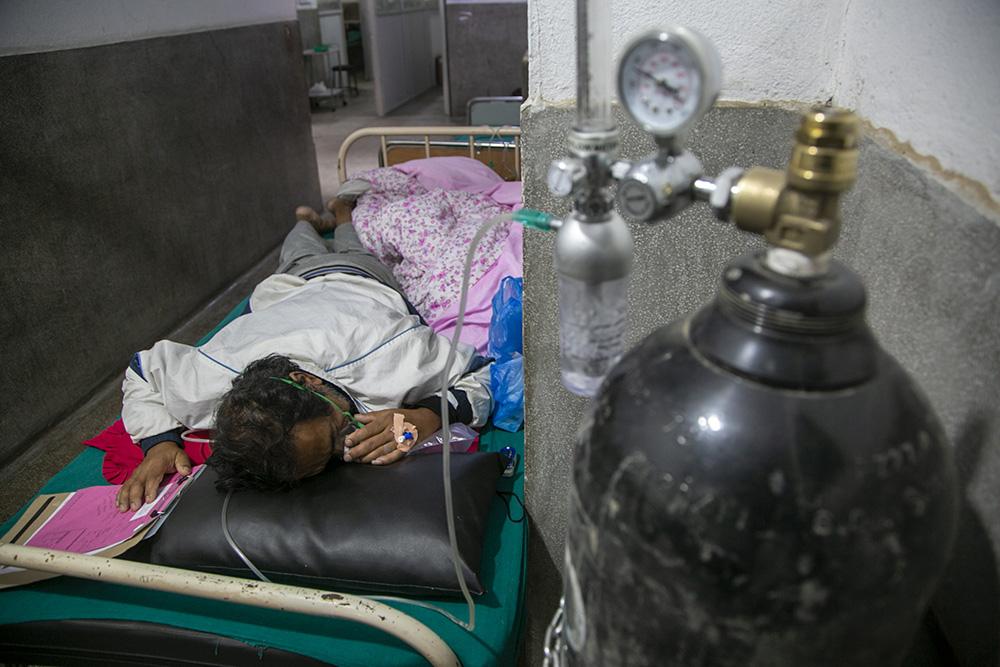 当地时间2021年5月5日,尼泊尔加德满都,一名新冠患者在医院的急诊走廊上吸氧。澎湃影像 图