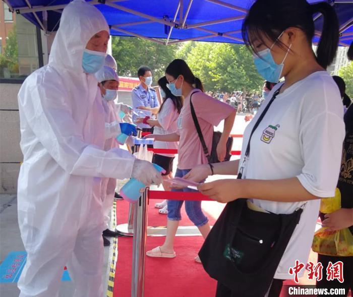 资料图:2020年7月7日,河南郑州,医务人员为进入考点的考生进行体温检查和消毒。河南省卫健委供图