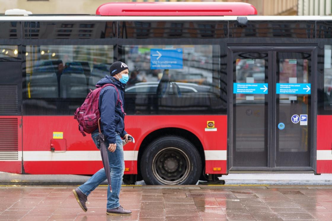 5月6日,在瑞典斯德哥尔摩,一名戴口罩的男子从公交车前走过。新华社 图
