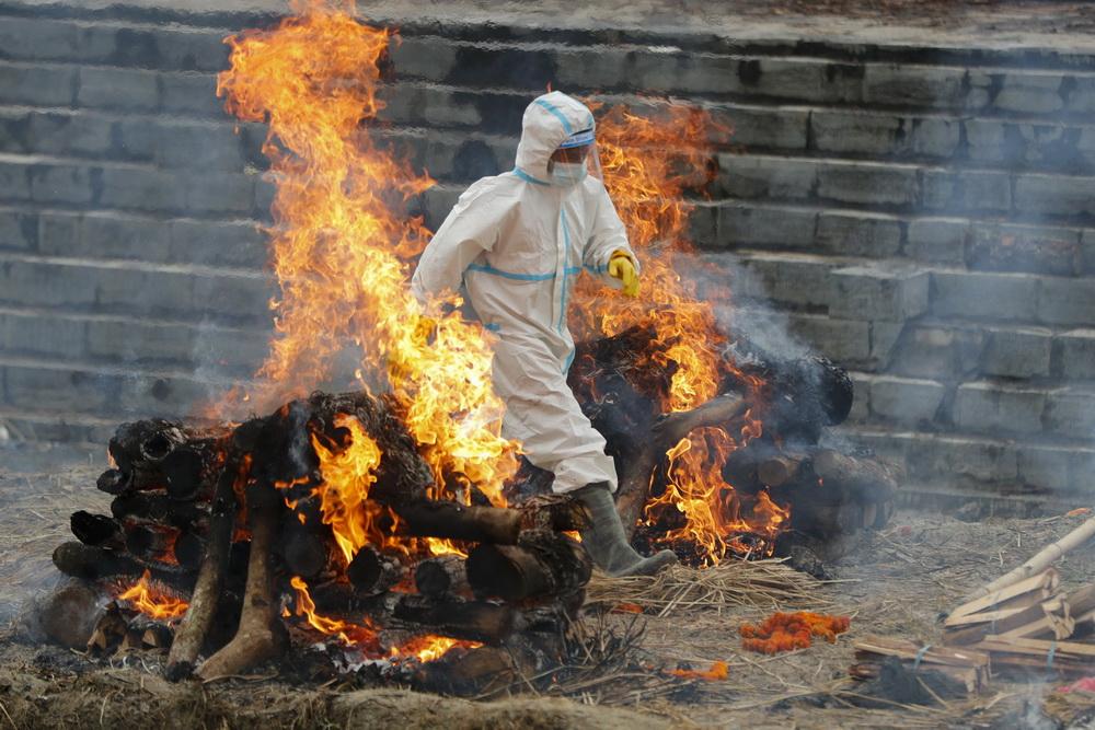 当地时间2021年5月5日,尼泊尔加德满都,工作人员穿着防护服,火化新冠死难者遗体。