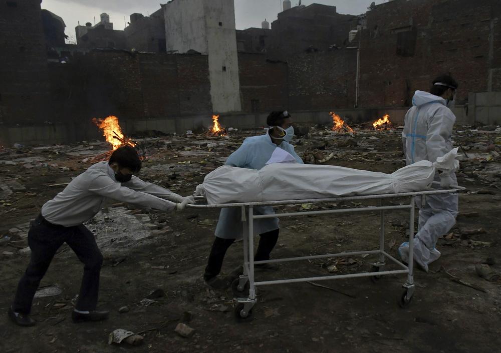 当地时间2021年5月7日,印度德里,工作人员将新冠逝者遗体运到火化点。