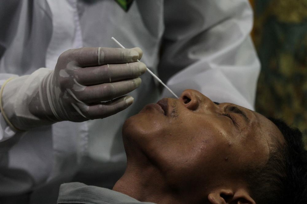 当地时间2021年5月6日,印度尼西亚亚齐省,医务工作者正在为民众采集鼻拭子样本,进行新冠病毒检测。据报道,印尼一机场医务人员重复使用鼻拭子,对机场旅客做新冠检测。据警方预计,这些拭子的重复使用次数或高达20000次,涉及旅客超9000人。目前,至少5名涉事人员被捕。