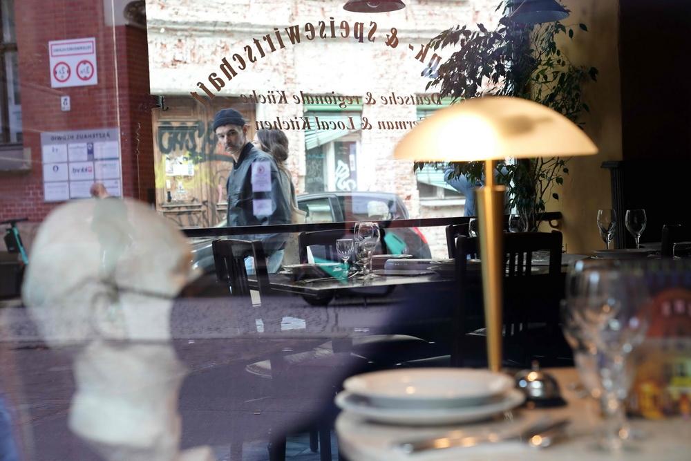 """当地时间2021年5月6日,德国柏林市中心一家餐厅在橱窗旁摆放了佩戴口罩、正在""""用餐""""的假人,吸引路人关注。德国联邦议院当日通过了联邦内阁提出的一项法案,将允许已完全接种疫苗人士和已从新冠感染中痊愈的人士在该国尚未""""解封""""的情况下,进行购物和聚会等活动时拥有更大的自由度。"""