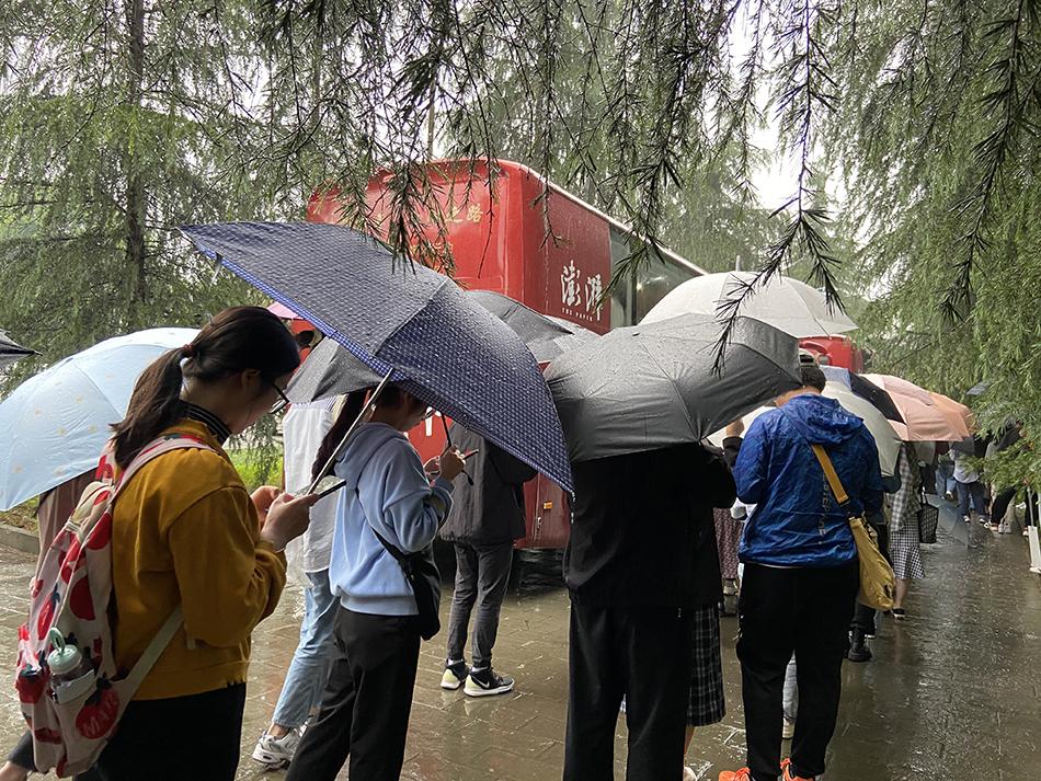 等候参观大巴的学生排起了长队。