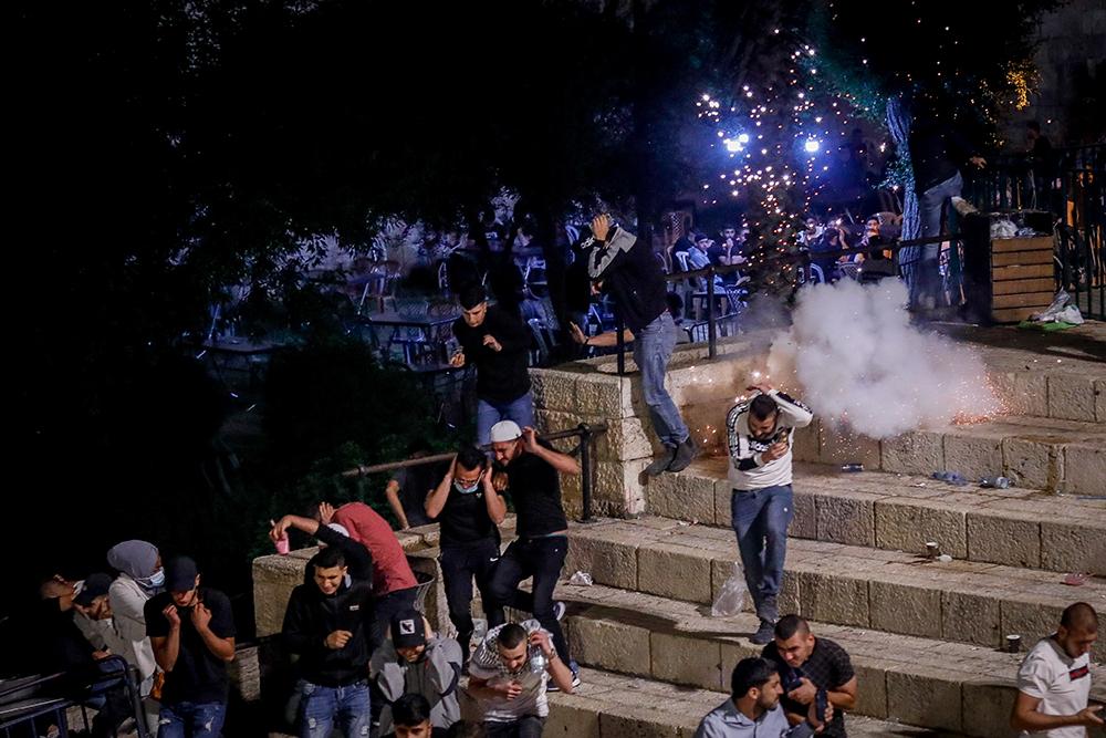 """当地时间2021年5月8日,闪光弹在耶路撒冷老城的冲突现场爆炸。7日晚间,成千上万的巴勒斯坦民众涌入东耶路撒冷阿克萨清真寺进行祈祷活动。其中有部分民众借此机会继续抗议以色列单方面宣布耶路撒冷为以色列""""首都""""并强迫迁离当地巴勒斯坦人的行为,这引发了抗议民众和该地区以色列警察的冲突。"""