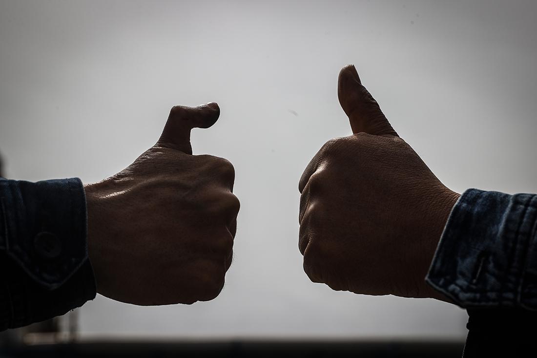 """王尚典(左)与同事一起做出""""赞""""的手势。今年41岁的王尚典是中国石油锦西石化公司车工高级技师、车工技能专家。他的右手拇指在2005年的一次加工事故中粉碎性断裂,被定为六级伤残,只能将左脚的第二个脚趾移植到手上。但他以异于常人的毅力重回车床旁,在2012年获得了第四届全国职工职业技能大赛车工冠军,被称为""""断指铁人""""。潘昱龙/新华社 图"""