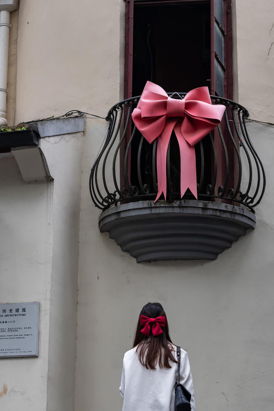"""近日,上海武康路上装饰着粉色蝴蝶结的阳台火了。此前,一位老奶奶在该阳台上向下打招呼的短视频在网络上走红。""""蝴蝶结阳台""""突然成为众多游客与市民的打卡地,不仅扰乱了奶奶的正常生活,也对周边居民造成困扰,居民呼吁,打卡不要影响他人的正常生活。目前,奶奶已被家人接走,蝴蝶结也已卸下了。"""