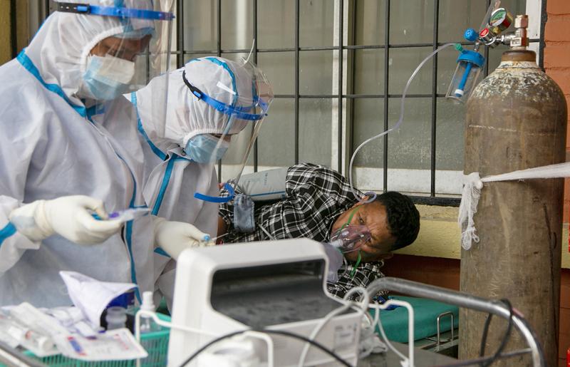 当地时间2021年5月10日报道,尼泊尔加德满都,新冠肺炎患者在病床上吸氧。鉴于尼泊尔第二拨疫情迅猛发展,导致氧气供给不足,尼泊尔登山协会要求正在雪山地区进行登山活动的人士将使用过的空氧气瓶带回。