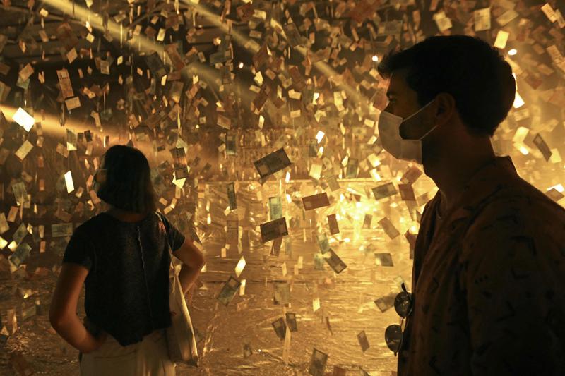 """当地时间2021年5月8日,黎巴嫩贝鲁特,游客参观当地艺术家设计的名为""""梦想银行""""的艺术展览,展厅内挂满写有""""0元""""的纸币,讽刺黎巴嫩货币严重贬值。"""