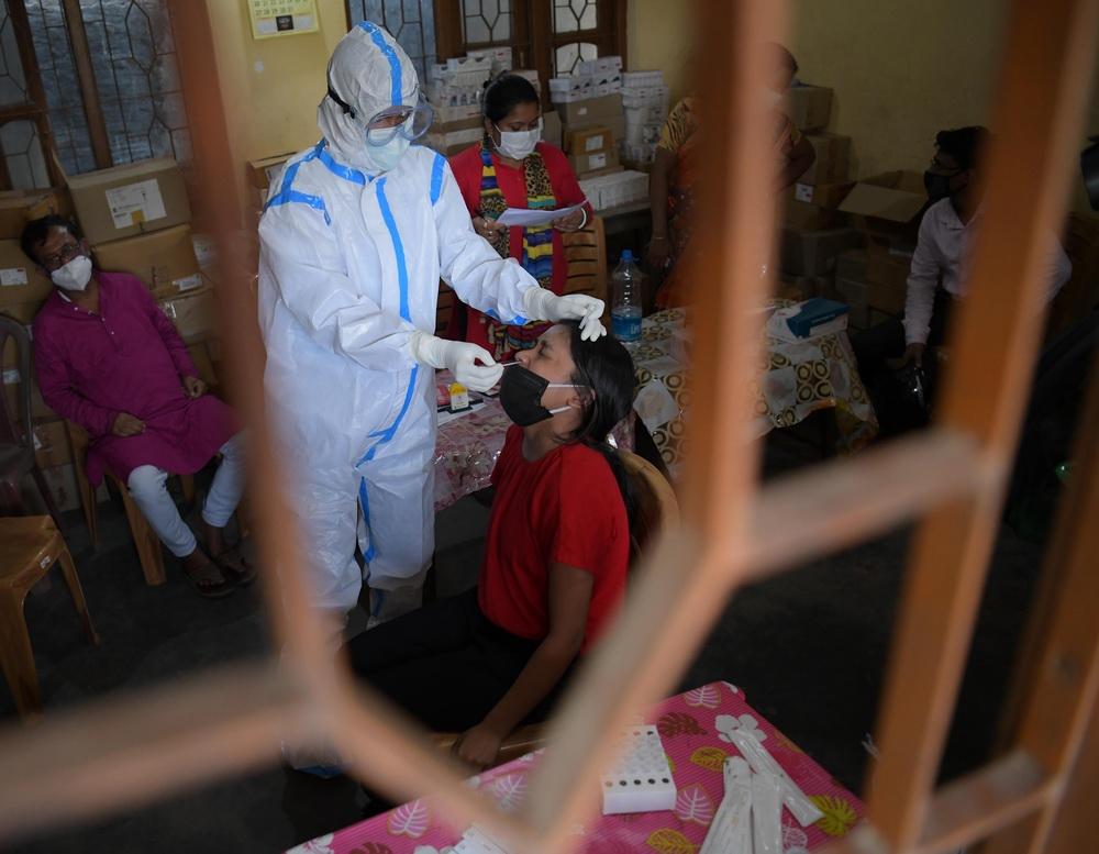 当地时间2021年5月11日,在印度阿加尔塔拉,医务人员为一名女子进行新冠检测取样。 印度卫生部11日公布的数据显示,印度单日新增新冠确诊病例329942例,累计病例22992517例;新增死亡病例3876例,累计死亡249992例。
