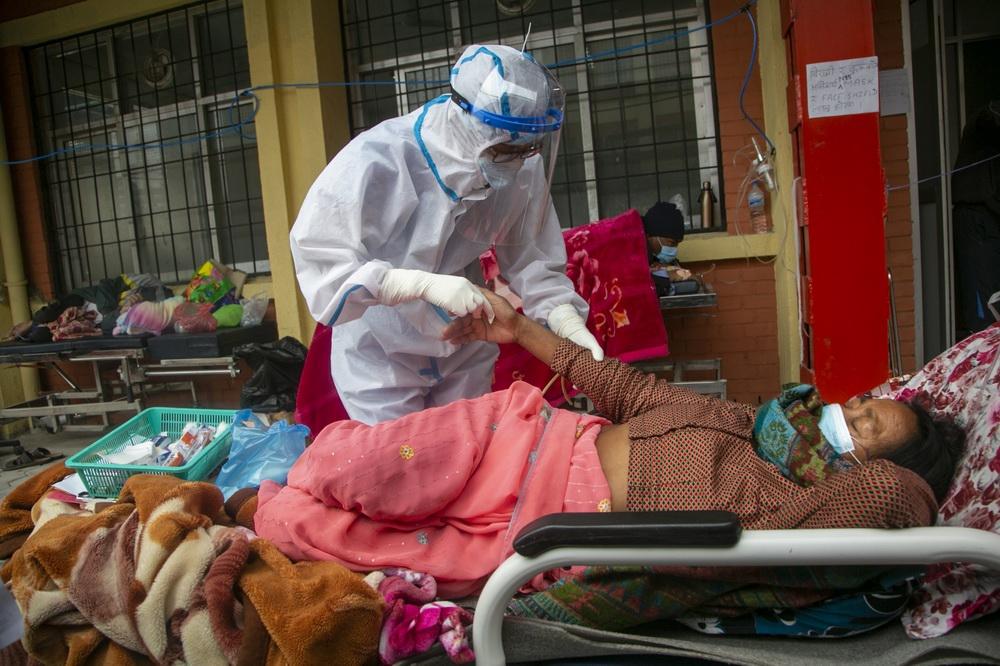 当地时间2021年5月10日,尼泊尔加德满都,医护人员照顾病房外的患者。