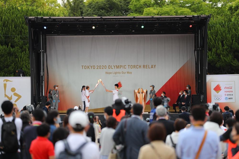 当地时间2021年5月11日,在日本福冈县福冈市,火炬手在点火仪式舞台上交接火炬。受新冠肺炎疫情影响,此次火炬传递取消火炬手路上跑动传递,改为举行点火仪式,由火炬手轮流在仪式的舞台上交接圣火,不允许普通观众入场观看。