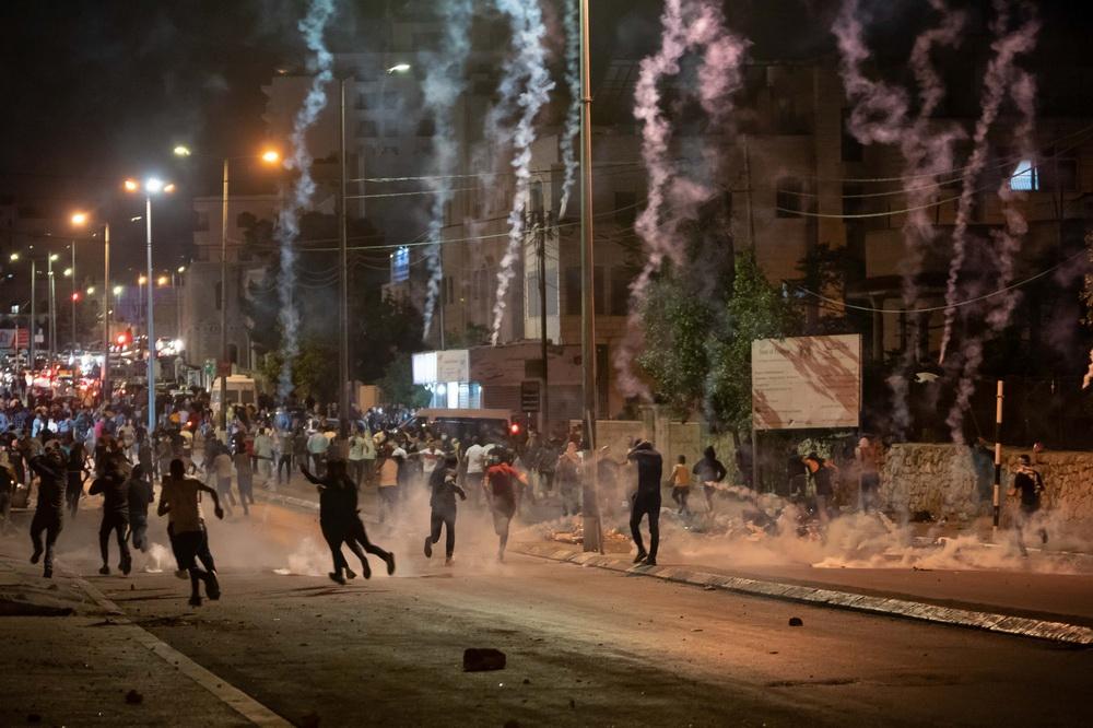 当地时间2021年5月11日,巴勒斯坦人在约旦河西岸城市伯利恒街头躲避以色列边防警察发射的催泪瓦斯。