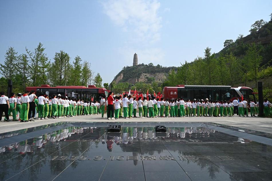 宝塔山下,东关小学四年级学生正排队参观澎湃新闻红色大巴车。 澎湃新闻记者 朱伟辉 摄
