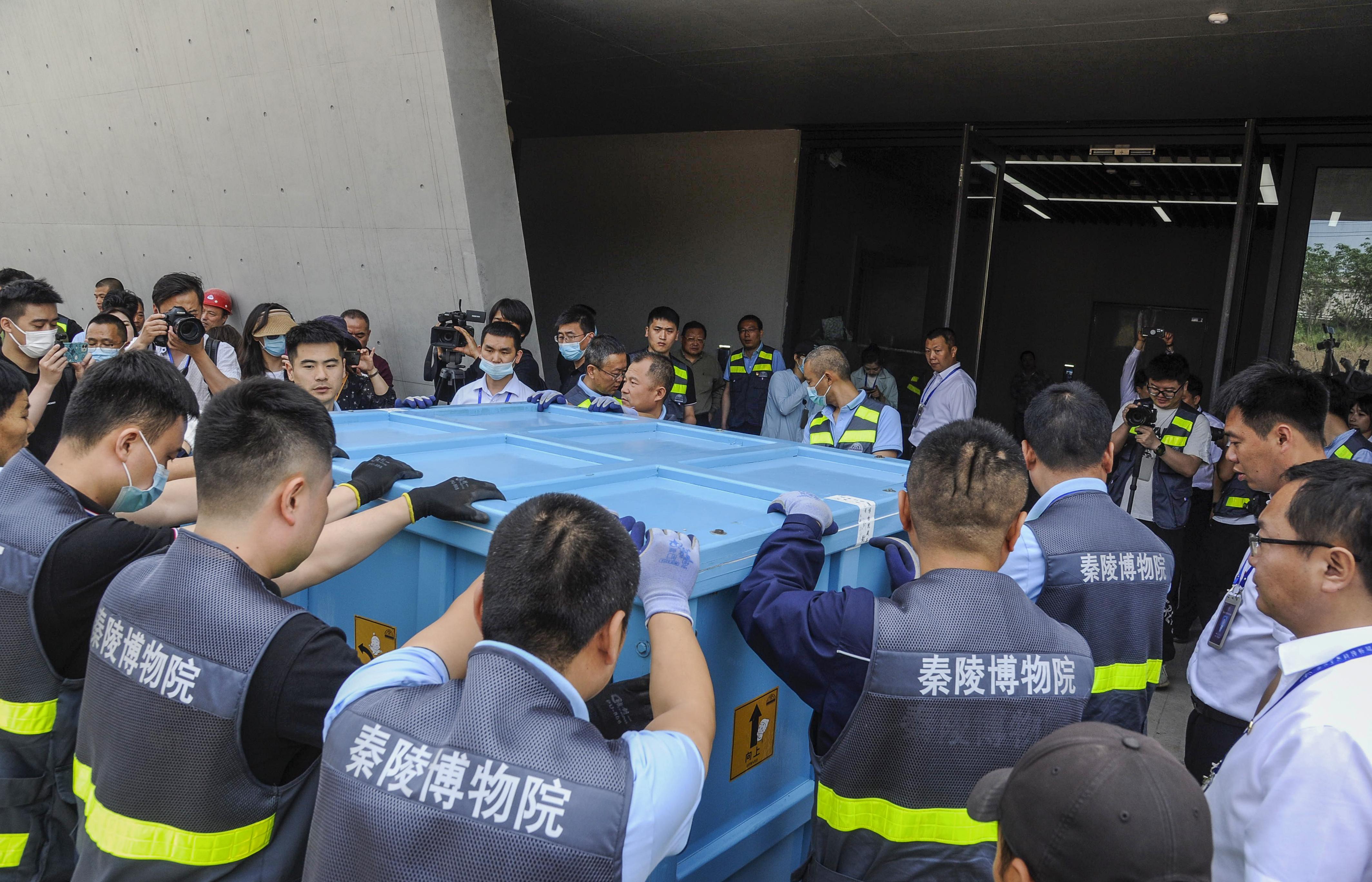 工作人员将卸下的箱子装上平板车推入馆中。随后,工作人员开始进行组装。
