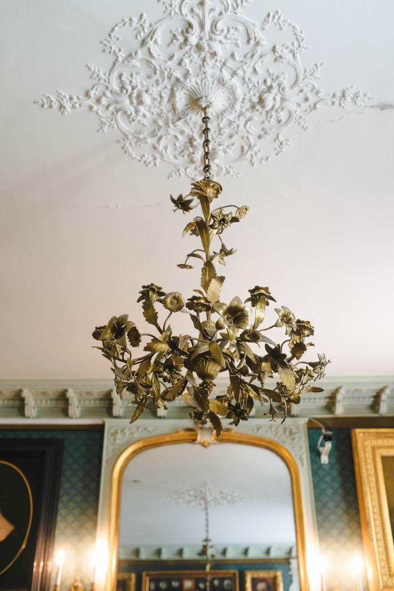 黄铜吊灯与纸灰粉饰的天花板相得益彰