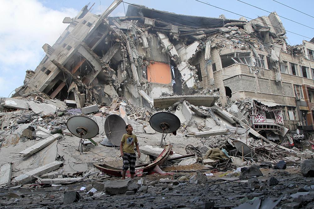 当地时间2021年5月13日,一名巴勒斯坦男孩查看以军空袭造成的破坏情况。5月10日至13日,以色列与加沙地带武装爆发严重冲突。加沙地带武装人员向以方发射1600余枚火箭弹,以军展开报复行动,空袭加沙地带武装组织约600个军事目标,并打死哈马斯多名高级指挥官。目前,双方冲突已导致以方7人死亡、100多人受伤,加沙地带67人死亡、近400人受伤。