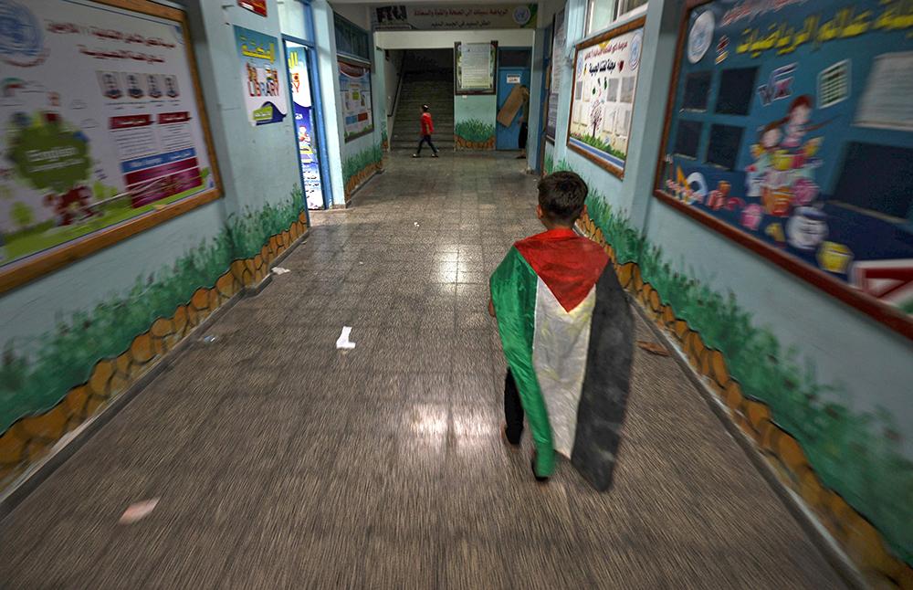 当地时间2021年5月13日,加沙,以色列持续轰炸加沙地带,巴勒斯坦男孩在一所联合国学校避难。