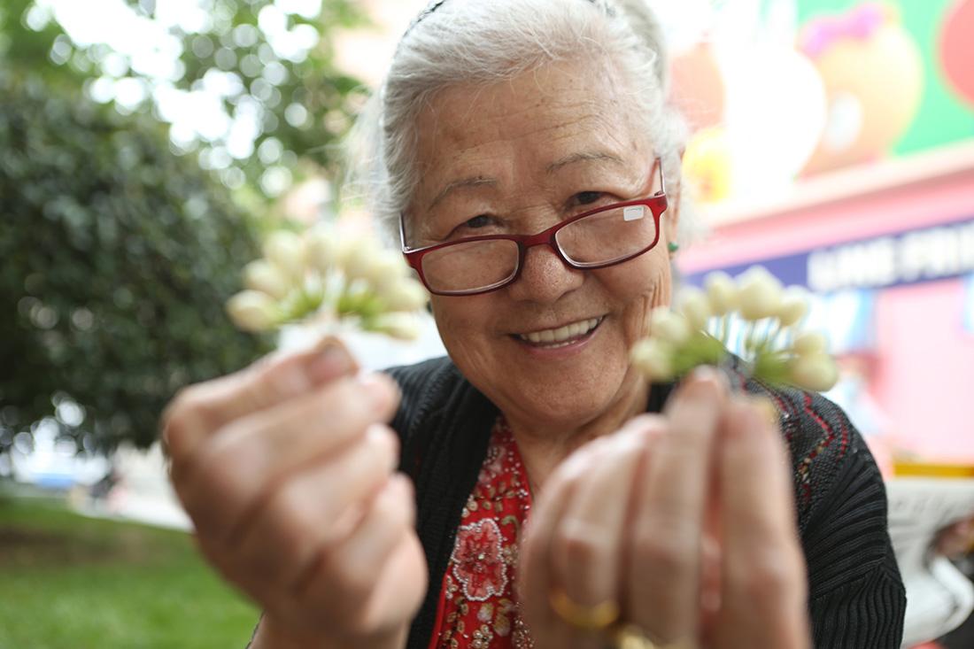 2020年5月23日,上海,淮海路,81岁的卖花王阿婆展示扎好的白兰花。