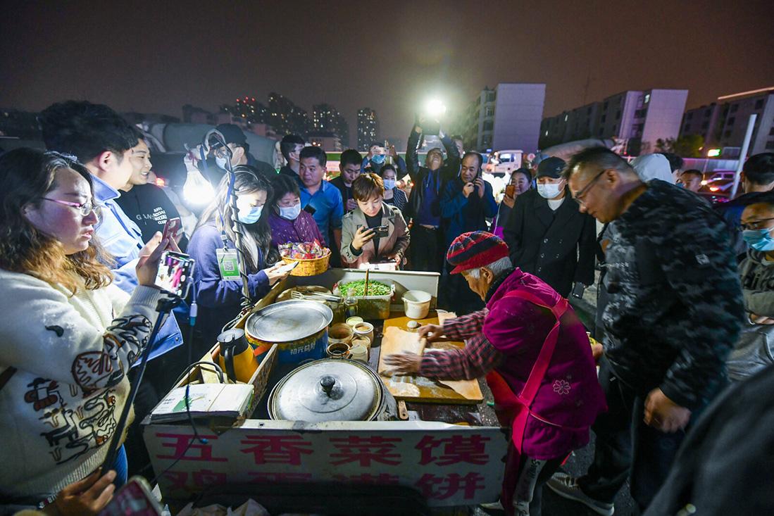 """2021年4月11日22时,河南郑州,96岁的""""煎饼奶奶""""准时出摊。老奶奶到后,大家将摊位团团围住,摊位前被围得水泄不通。"""