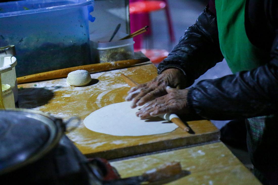 2019年11月21日凌晨,河南郑州,每天子夜到凌晨在路边摆摊卖煎饼的张姓老人。