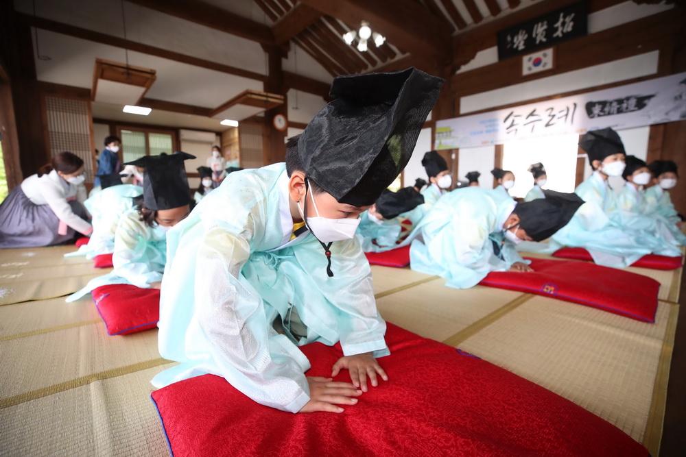 当地时间2021年5月14日,韩国大邱,韩国教师节将至,小学生们穿着传统服装学习束脩礼。束脩礼是古代学生怀着尊敬的心情向老师求教的礼节。