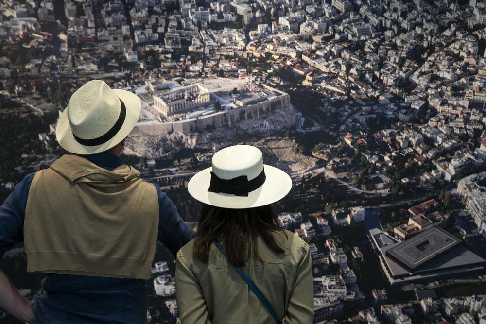 当地时间2021年5月14日,希腊雅典,参观者在雅典卫城博物馆内观看雅典的航拍照片。当地时间14日雅典卫城博物馆重新向公众开放,人们在博物馆开放第一天进入参观。