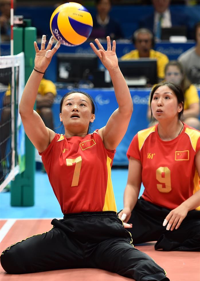 王亚男(左)代表中国残奥坐式排球队出战。