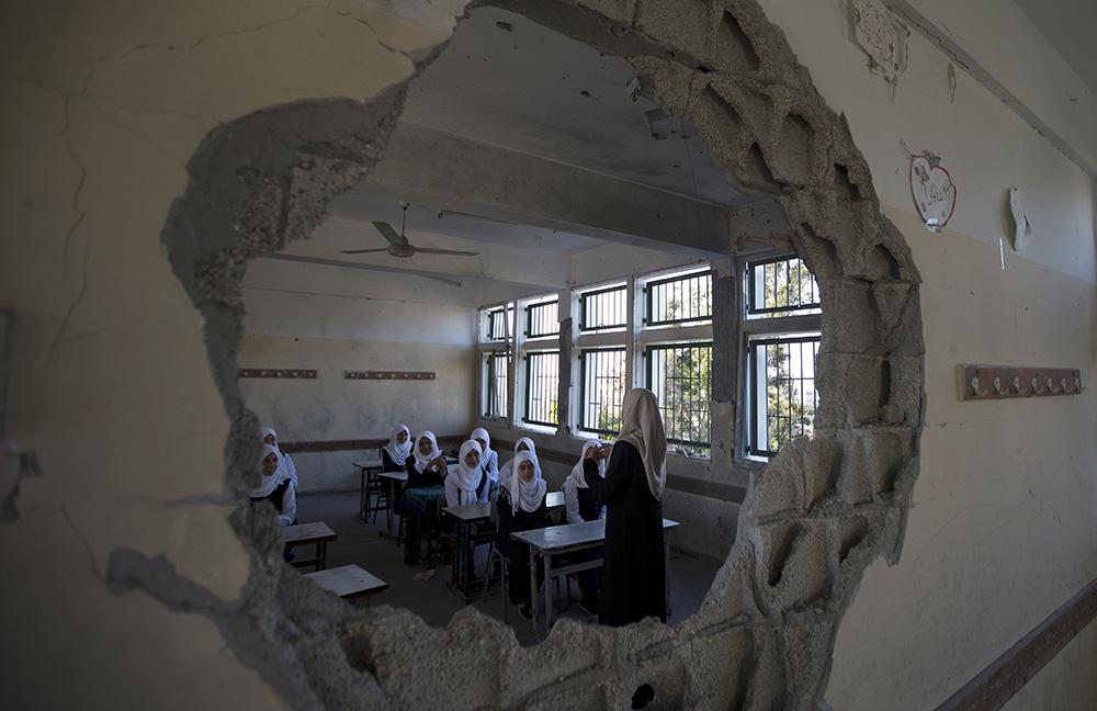 当地时间2014年9月14日,加沙,巴勒斯坦学生迎来开学第一天,他们穿过废墟,在以色列炮击中被破坏的学校上课。人民视觉 资料图