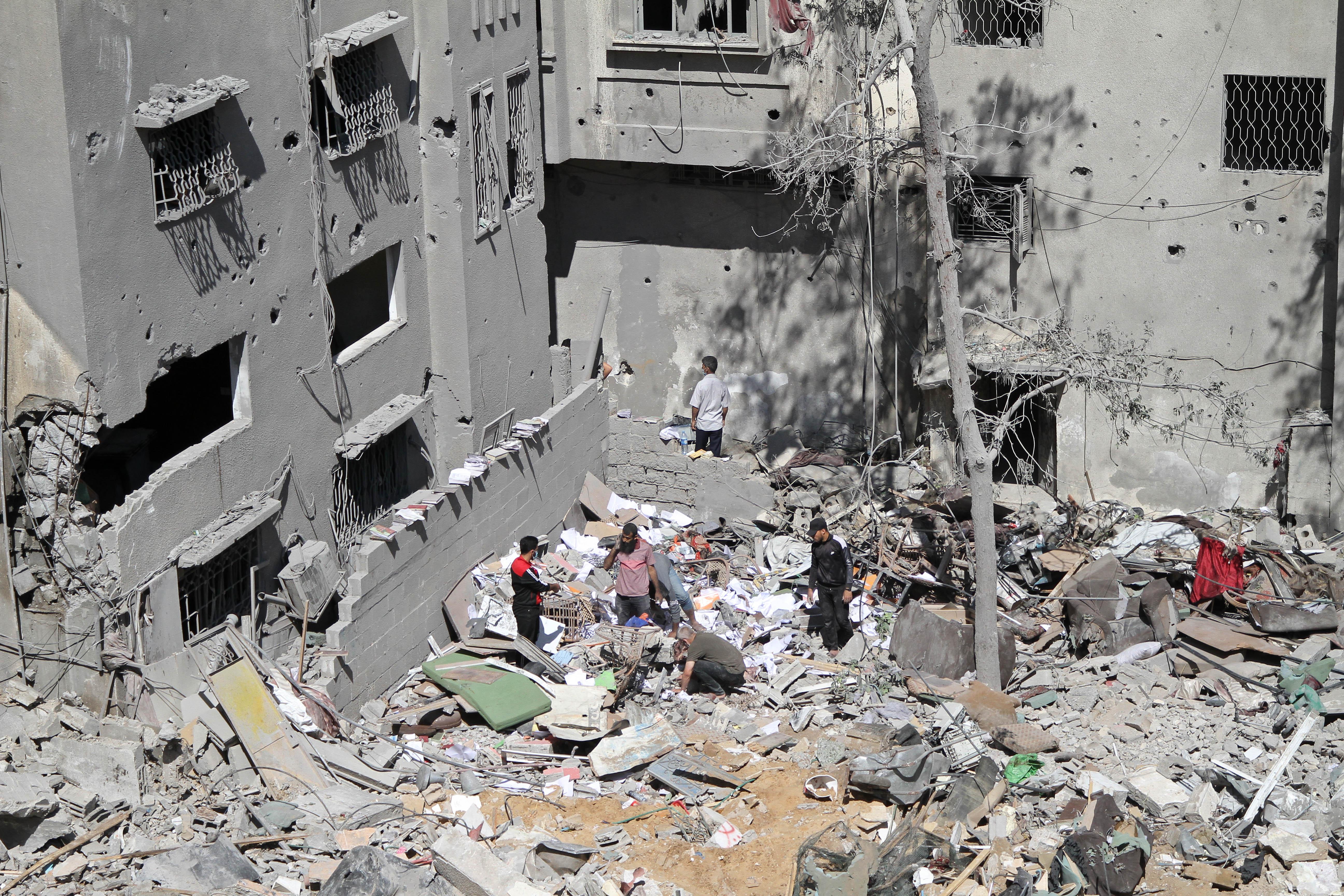 当地时间5月15日,巴勒斯坦人站在空袭过后的位于加沙城西部的沙提难民营废墟间。新华社 图
