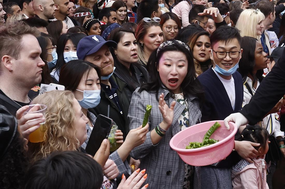 """2021年5月15日,一位观众拒绝品尝参赛选手比赛用辣椒。当日,2021年辣节活动在北京举行,活动中进行了吃辣椒比赛。辣节活动现场不仅提供各类浓郁异域风情的""""火辣""""食品,参加者也可体验各式与""""辣""""相关的创意和巧思。侯宇/中新社 图"""