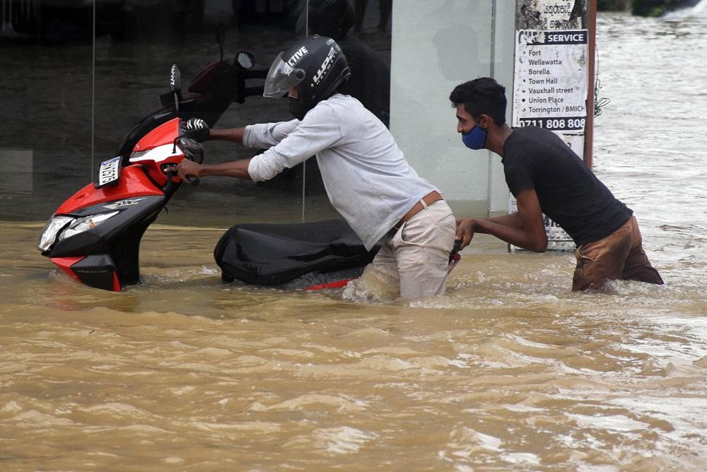 当地时间2021年5月15日,人们在斯里兰卡加姆珀哈涉水前行。
