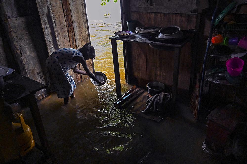 当地时间2021年5月15日,斯里兰卡科伦坡,当地持续的暴雨淹没了许多低洼地区,一个女孩在被淹的房子内洗盘子。斯里兰卡灾害管理中心15日发布最新天气报告称,由于孟加拉湾形成的超级气旋,持续数日的强风暴雨已造成至少4人死亡,超过4.2万人受到影响。