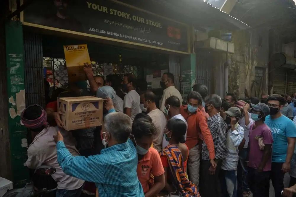 当地时间2021年5月15日,民众在印度西孟加拉邦实施全面防疫封锁前排队买酒。 印度西孟加拉邦政府15日宣布,从5月16日至30日实施全面防疫封锁措施,以遏制新冠疫情蔓延。
