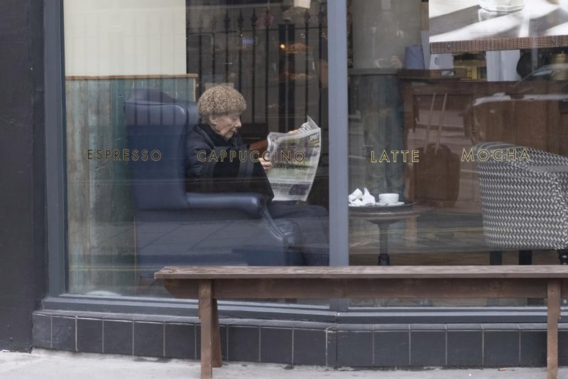 """当地时间2021年5月17日,英国伦敦,一名顾客在一家咖啡馆看报。当日起,英国政府按照路线图进一步放宽英格兰地区为防控新冠疫情而实施的""""禁足""""措施。"""