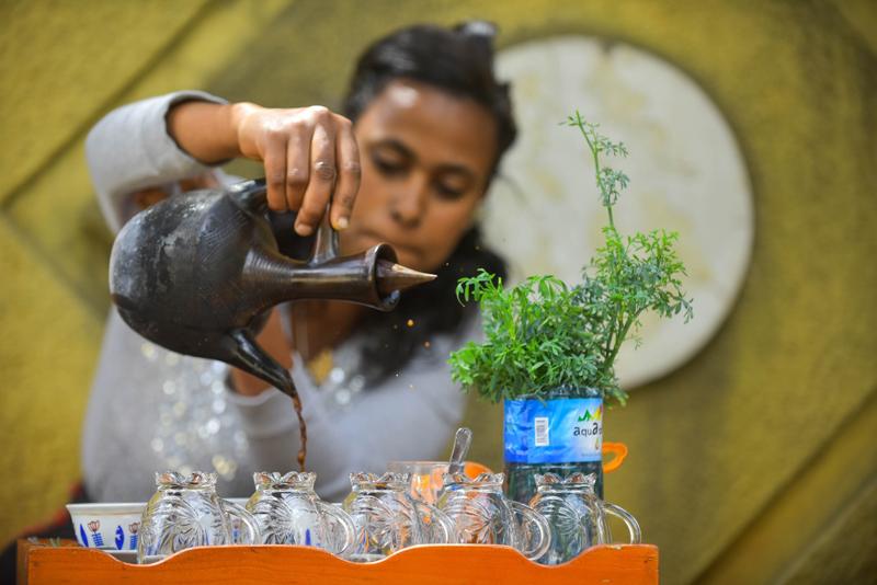 """当地时间2021年5月17日,埃塞俄比亚亚的斯亚贝巴,一名女商贩在街头的咖啡摊等待顾客。埃塞俄比亚有""""咖啡的故乡""""之称,是世界上重要的咖啡生产国。许多当地咖啡爱好者喜欢和亲友聚在街头,花上数个小时品尝咖啡,边喝边聊。"""
