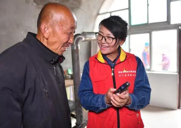 国网陕西张思德(延安枣园)共产党员服务队党支部书记、队长卜燕萍(右一)走访当地群众