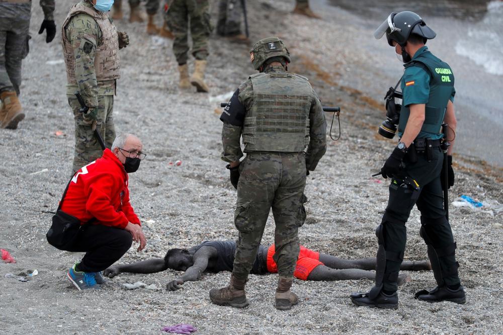 5月18日,士兵和红十字会工作人员在西班牙飞地休达照看一名上岸的移民。