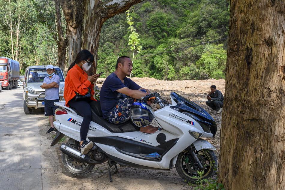 2021年5月31日,云南省玉溪市红塔区玉溪大河附近,等待恢复交通后回家的居民。