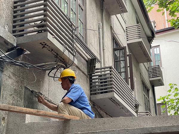 5月26日,建筑工人在对南昌路74弄的墙壁进行保护性修缮。
