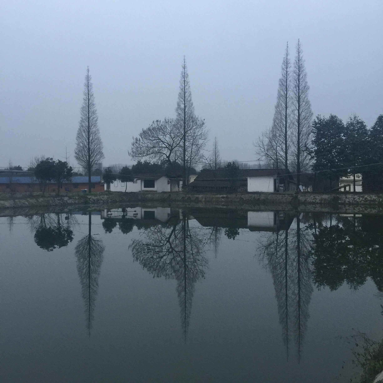 家乡雪白的房子映在水里。