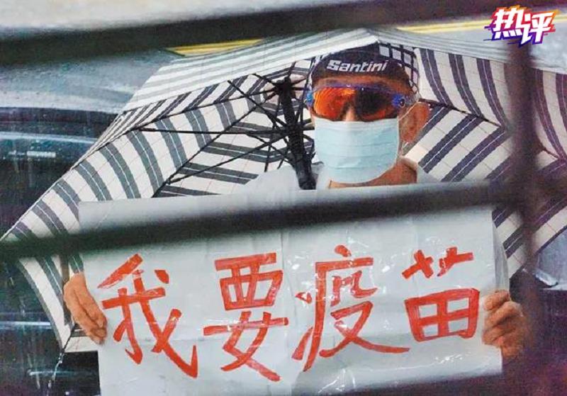"""台湾民众拿着""""我要打疫苗""""的牌子"""