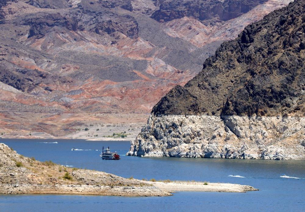 """当地时间2021年6月12日,美国内华达州米德湖国家休闲区,包括""""沙漠公主""""号在内的船只巡游在布满矿物的岩石前。北美最大的人工水库米德湖海拔下降至1,071.53英尺,这是自1937年胡佛大坝建成后蓄水以来的最低水平。水位下降是过去20年持续干旱以及美国西南部对水需求增加的结果。"""