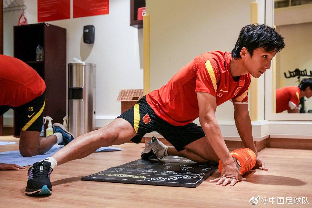 国足球员进行身体拉伸。