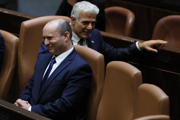 当地时间2021年6月13日,纳夫塔利·贝内特(前)和亚伊尔·拉皮德(后)在位于耶路撒冷的以色列议会出席就新一届政府组建方案进行投票的特别会议。