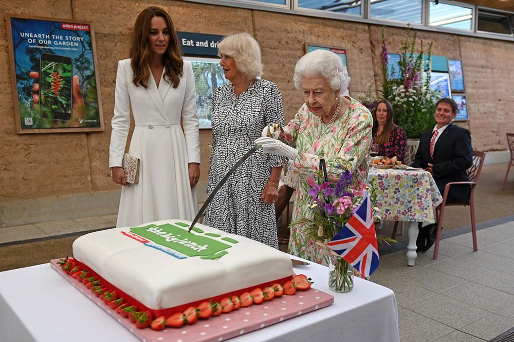 当地时间2021年6月11日,英国康沃尔,英国女王伊丽莎白二世在凯特王妃和卡米拉的陪同下,出席G7峰会的活动,用一把礼仪用剑将一块大蛋糕切开。蛋糕旁边放有一把传统刀具,在进行尝试之后,女王最终还是用传统刀具完成了切蛋糕的仪式。