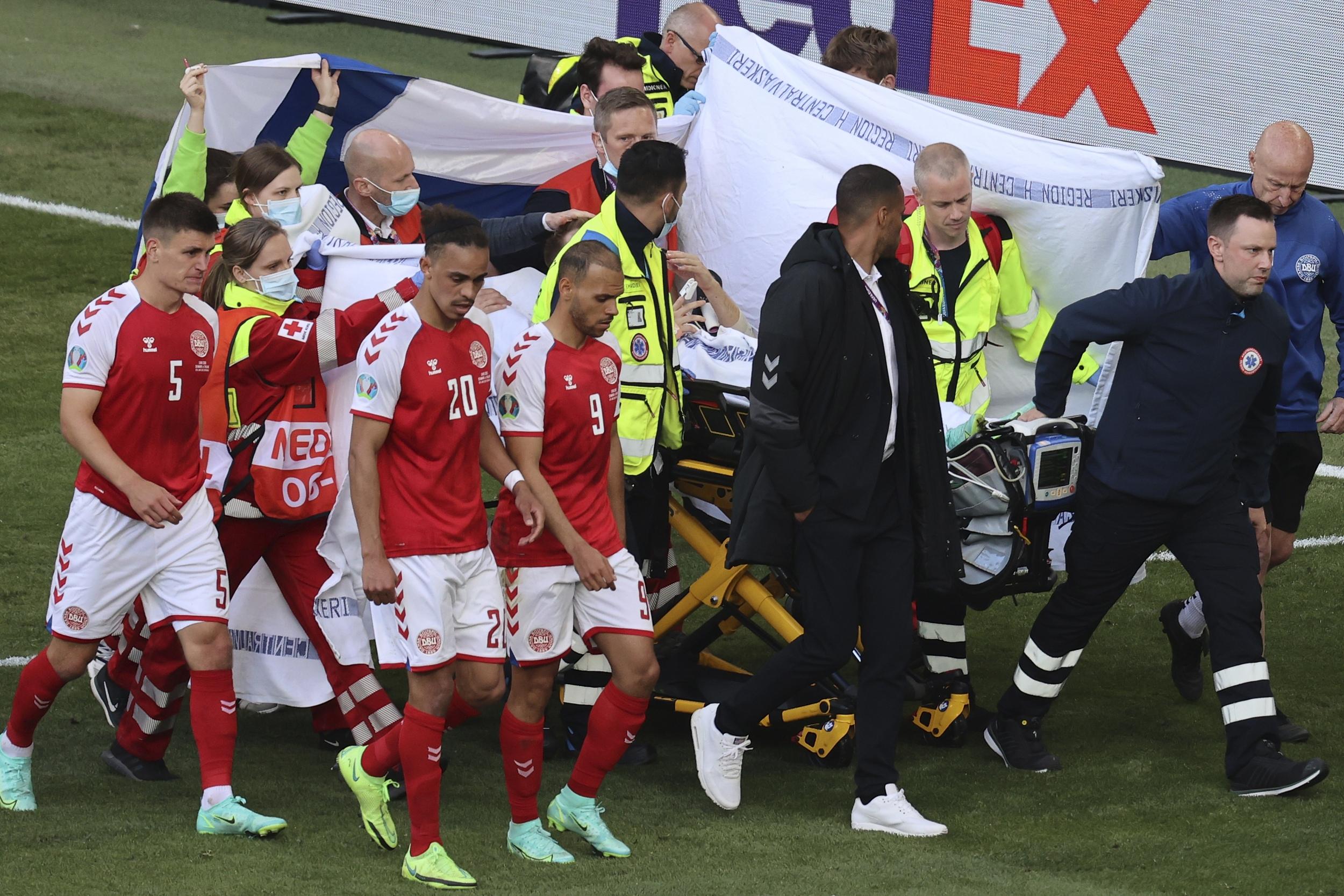 丹麦球员护送埃里克森离场。